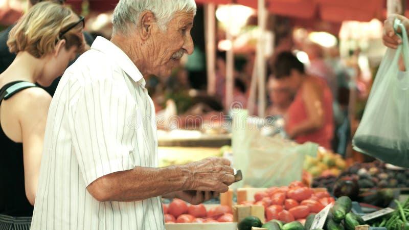 PULA, CROATIA - AUGUST 4, 2017. Senior man buying vegetables at local marketplace stock photo