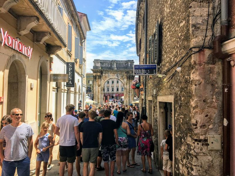A nice summer day in the town of Pula, Croatia with the Triumphal Arch of the Sergi in background. Pula, Croatia - July 4th, 2019: Tourists walking down Giardini stock photography