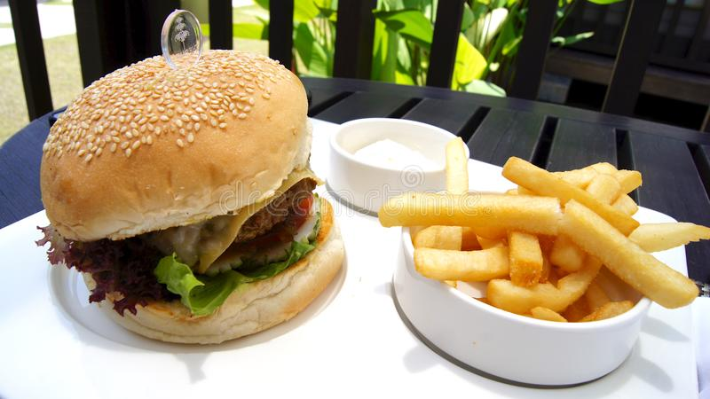 PULAU凌家卫岛,马来西亚- 2015年4月5日:乳酪汉堡和炸薯条在一块白色板材在一家豪华旅馆餐馆 库存照片