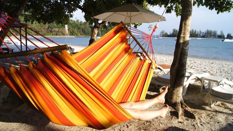 PULAU LANGKAWI, MALEISIË - 5 APRIL 2015: Vrouw het ontspannen in de hangmat bij het strand stock foto