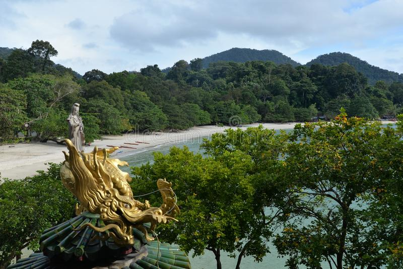 Pulau Pangkor Island, Malaysia. Teluk Nipah beach and Chinese temple. Teluk Nipah sandy tropical beach, Pulau Pangkor island, Malaysia. Golden statue on a royalty free stock photos