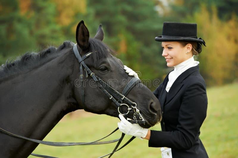 Puleggia tenditrice dell'amazzone in uniforme con il cavallo immagini stock