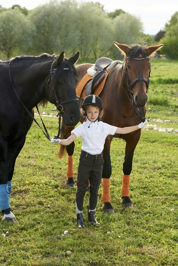 Puleggia tenditrice della bambina che comunica con i suoi cavalli in attrezzatura professionale fotografie stock libere da diritti