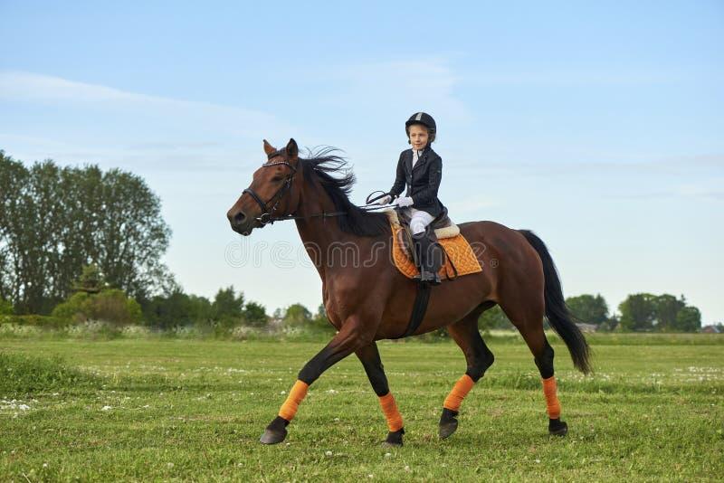 puleggia tenditrice della bambina che monta un cavallo attraverso paese in attrezzatura professionale fotografie stock libere da diritti