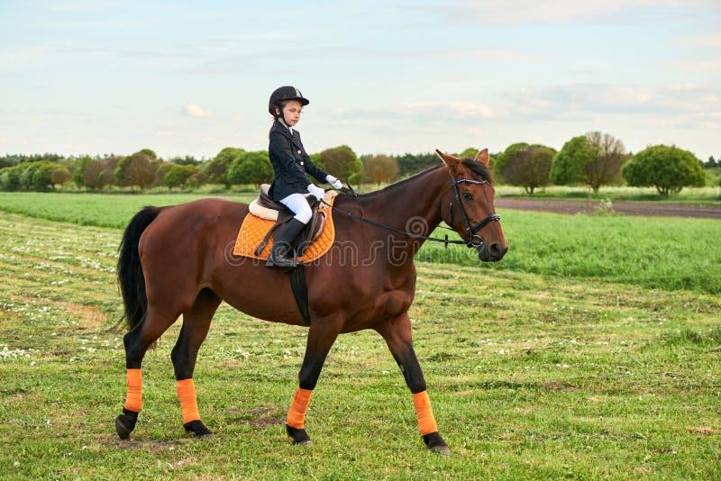 puleggia tenditrice della bambina che monta un cavallo attraverso paese in attrezzatura professionale fotografia stock libera da diritti