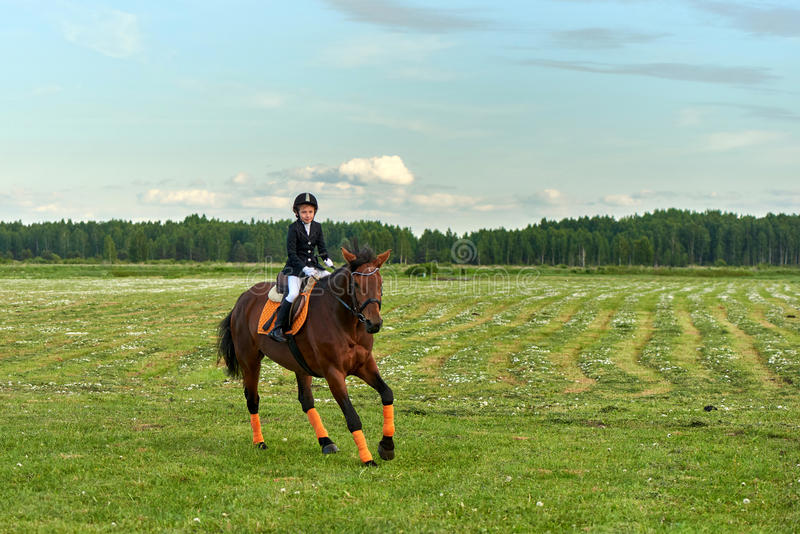 puleggia tenditrice della bambina che monta un cavallo attraverso paese in attrezzatura professionale fotografie stock