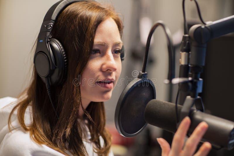 Puleggia tenditrice femminile Talking On Microphone in studio radiofonico fotografia stock
