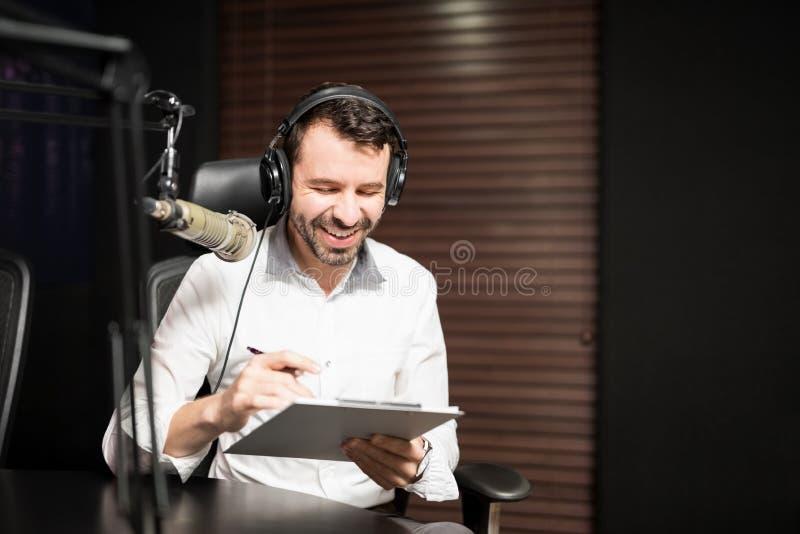 Puleggia tenditrice radiofonica che intervista un ospite dallo studio fotografie stock libere da diritti