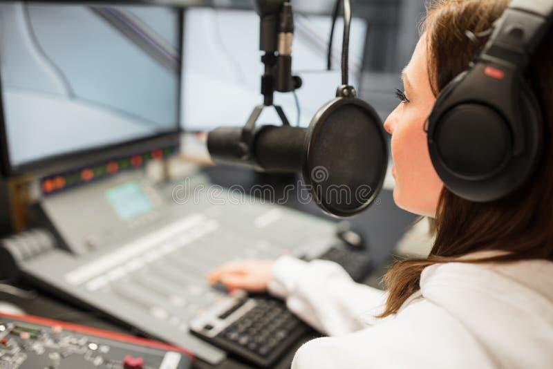 Puleggia tenditrice Wearing Headphones While che utilizza microfono nella radio Statio fotografia stock libera da diritti
