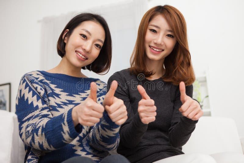 Pulgar asiático joven de la demostración de la mujer dos imagen de archivo libre de regalías