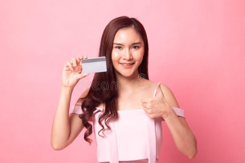 Pulgar asiático joven de la demostración de la mujer para arriba con una tarjeta en blanco imágenes de archivo libres de regalías