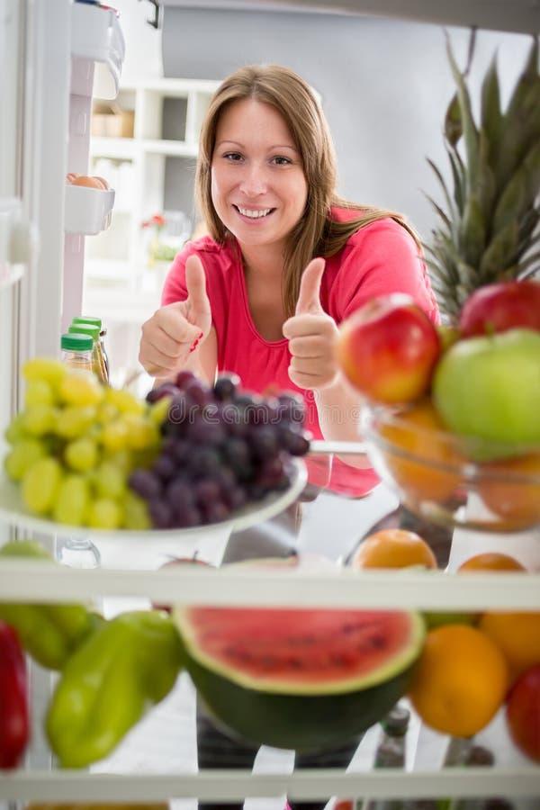 Pulgar de la demostración de la mujer para arriba para la comida sana imágenes de archivo libres de regalías