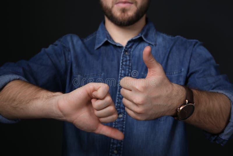 PULGAR de la demostración del hombre arriba y abajo del gesto en lenguaje de signos en fondo negro foto de archivo libre de regalías