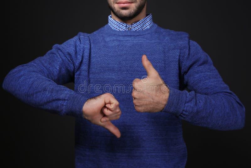 PULGAR de la demostración del hombre arriba y abajo del gesto en lenguaje de signos en fondo negro foto de archivo