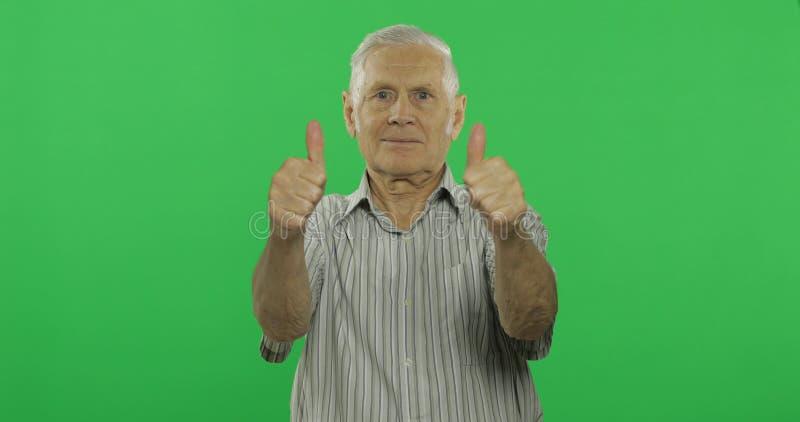 Pulgar de la demostración del hombre mayor para arriba y sonrisas Viejo hombre hermoso en el fondo dominante de la croma fotografía de archivo