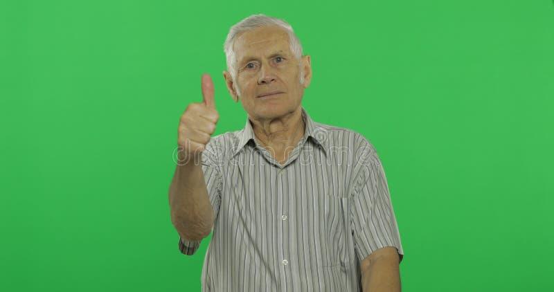 Pulgar de la demostración del hombre mayor para arriba y sonrisas Viejo hombre hermoso en el fondo dominante de la croma fotos de archivo libres de regalías