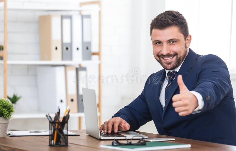 Pulgar de la demostración del hombre de negocios para arriba, usando el ordenador portátil en oficina fotografía de archivo libre de regalías