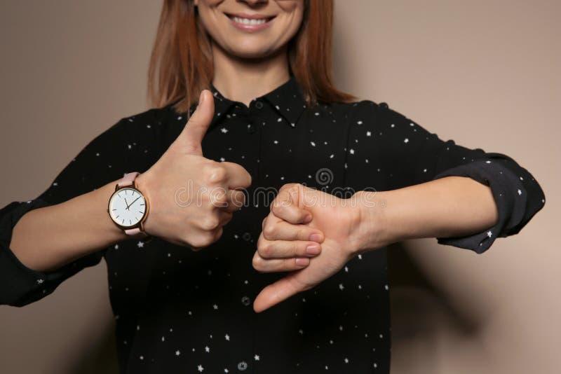PULGAR de la demostración de la mujer arriba y abajo del gesto en lenguaje de signos en fondo del color imágenes de archivo libres de regalías