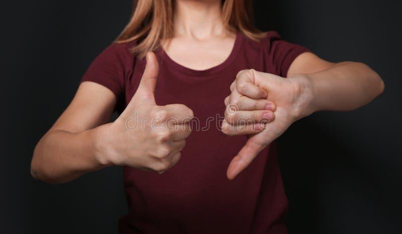 PULGAR de la demostración de la mujer arriba y abajo del gesto en lenguaje de signos en fondo negro fotografía de archivo