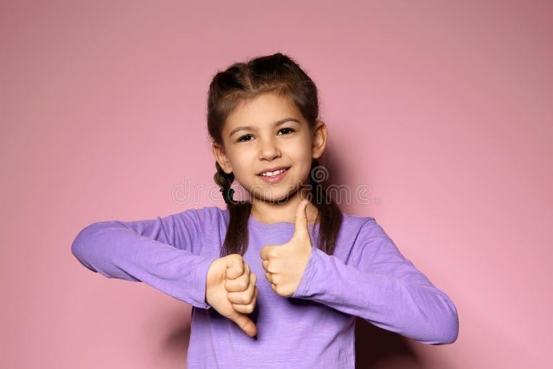 PULGAR de la demostración de la niña arriba y abajo del gesto en lenguaje de signos imágenes de archivo libres de regalías
