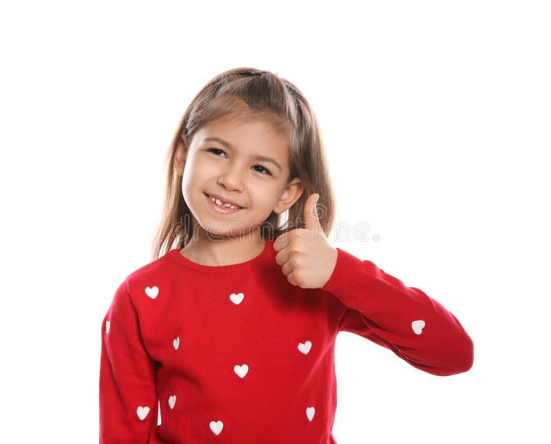 PULGAR de la demostración de la niña ENCIMA del gesto en lenguaje de signos en blanco foto de archivo