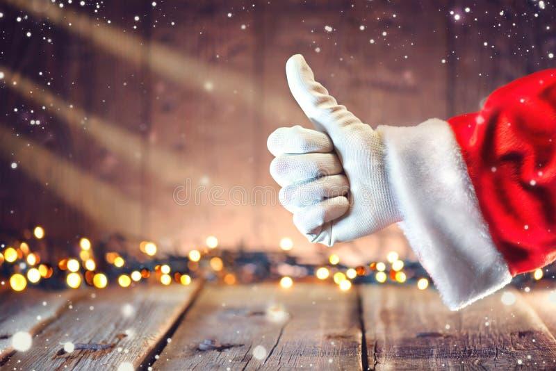 Pulgar de Santa Claus encima del gesto sobre fondo de la Navidad imagenes de archivo