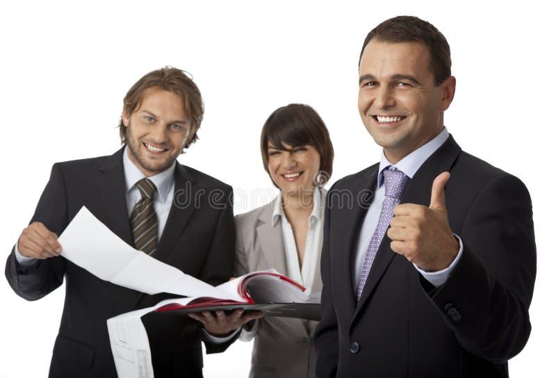 Pulgar de tres empresarios para arriba imagen de archivo
