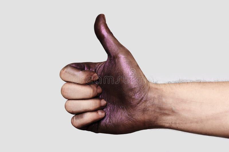 Pulgar encima de la mano con la pintura púrpura del maquillaje fotos de archivo