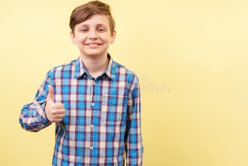 Pulgar entusiasta sonriente feliz de la demostración del muchacho para arriba foto de archivo