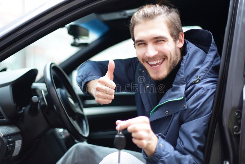 Pulgar feliz de la demostración del hombre para arriba y las llaves a su coche fotografía de archivo