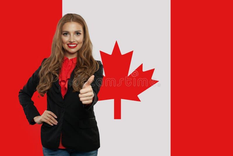 Pulgar feliz de la demostración de la mujer joven para arriba contra la bandera de Canadá imagenes de archivo