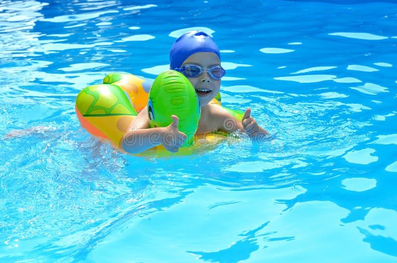 Pulgar para arriba del niño en piscina imagenes de archivo