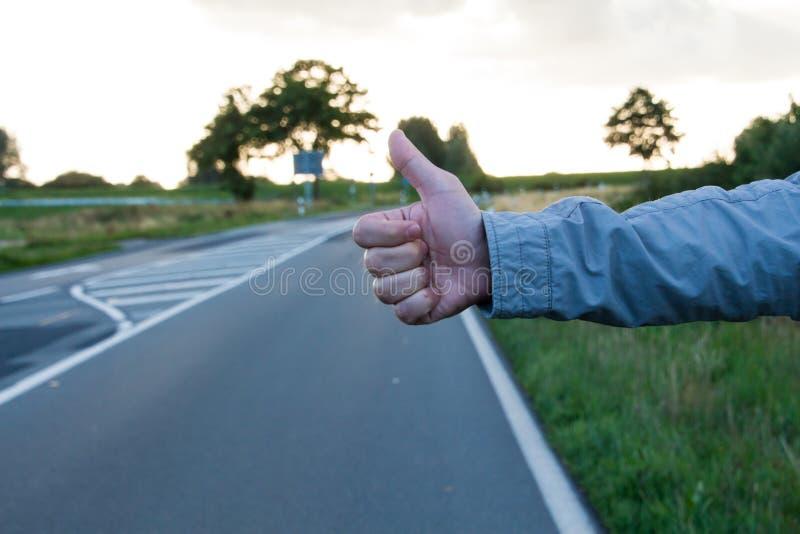 Pulgar para arriba en un camino mientras que hace autostop imagenes de archivo