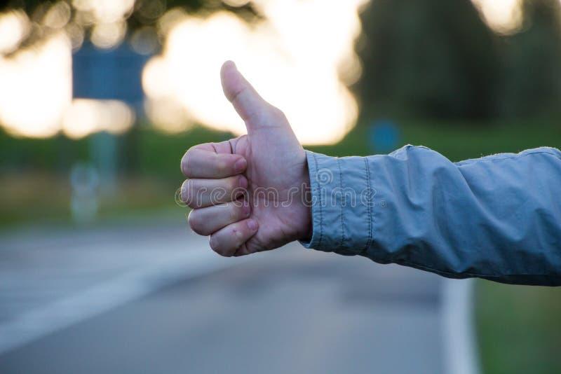 Pulgar para arriba en un camino mientras que hace autostop fotografía de archivo