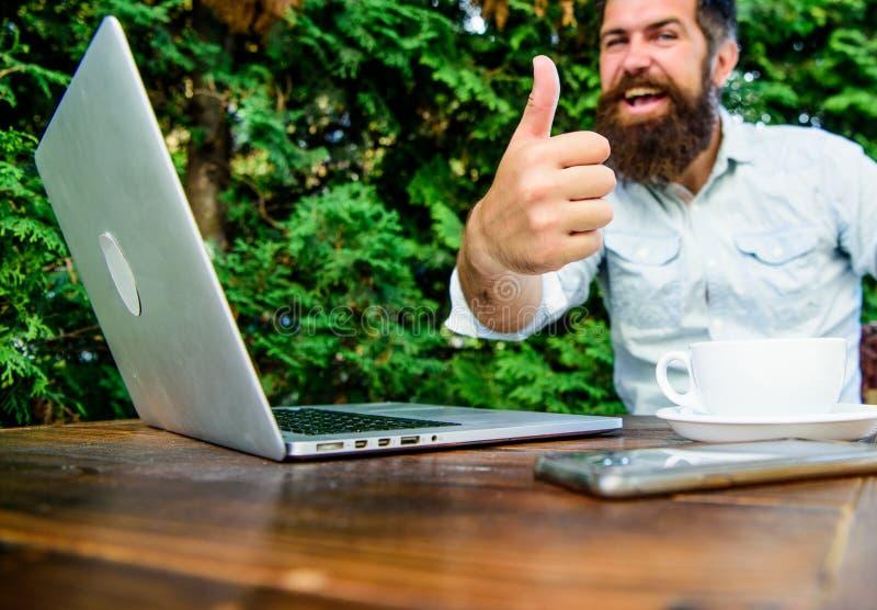 Pulgar para arriba inconformista barbudo brutal en el descanso para tomar caf? En fondo verde Hombre de negocios acertado Negocio fotos de archivo