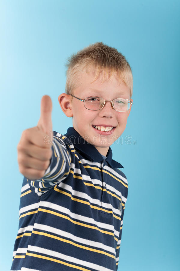 Pulgar sonriente de la demostración del adolescente encima de la muestra imagenes de archivo
