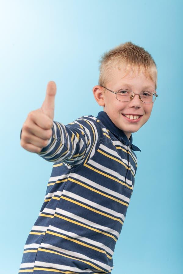 Pulgar sonriente de la demostración del adolescente encima de la muestra imagen de archivo libre de regalías