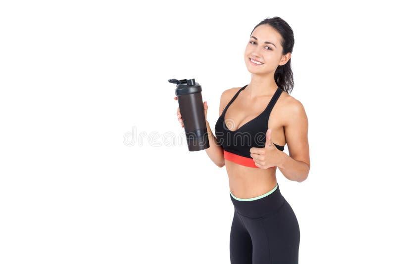 Pulgar sonriente encima de la muchacha con la botella de agua imagen de archivo