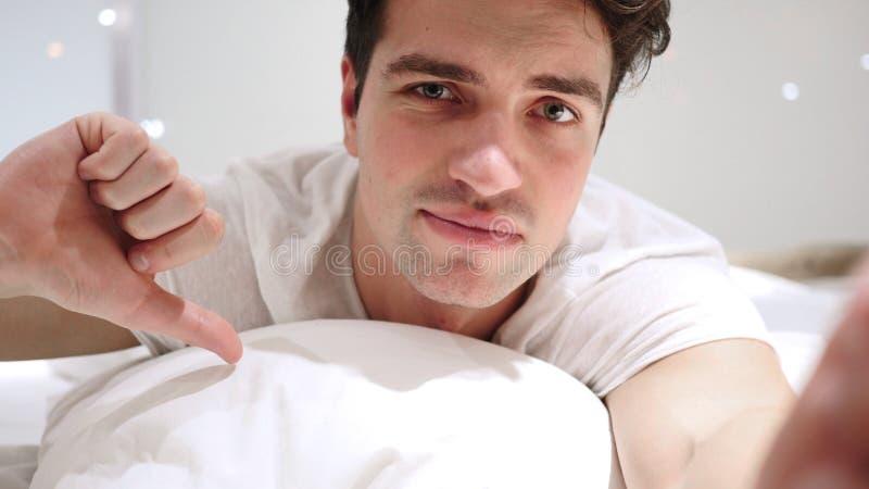 Pulgares abajo por el hombre que miente en cama en el estómago, teniendo aversión fotografía de archivo libre de regalías