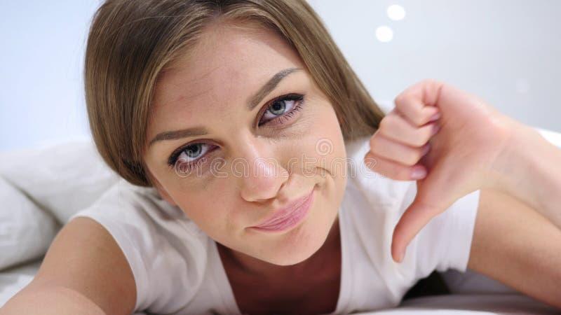 Pulgares abajo por la mujer que miente en cama en el estómago, teniendo aversión fotografía de archivo