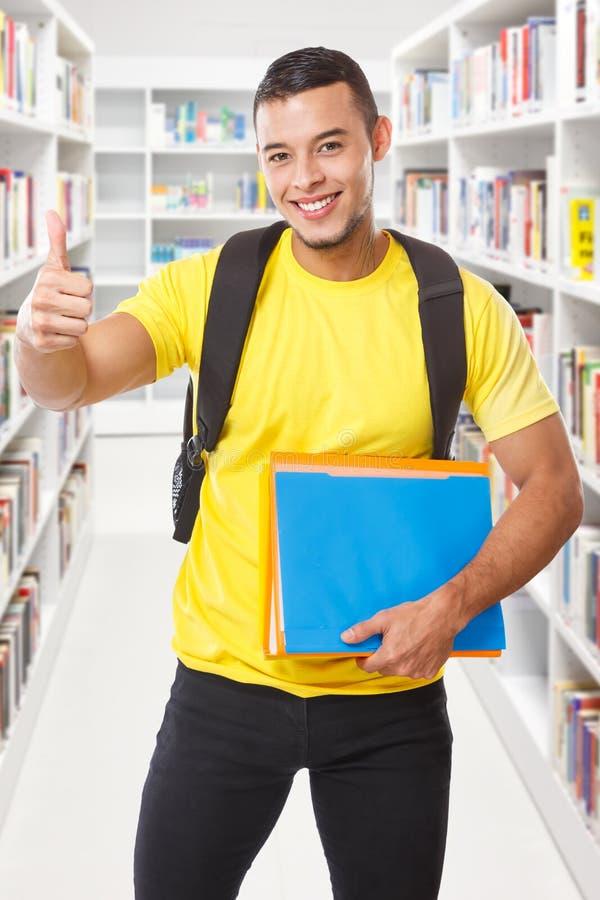 Pulgares acertados del éxito del estudiante encima de la biblioteca que aprende a gente sonriente del formato de retrato imágenes de archivo libres de regalías