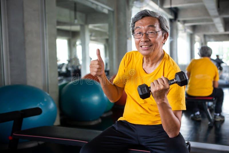 Pulgares de elevación de las pesas de gimnasia y de la demostración del hombre asiático mayor del deporte para arriba en gimnasio imagenes de archivo