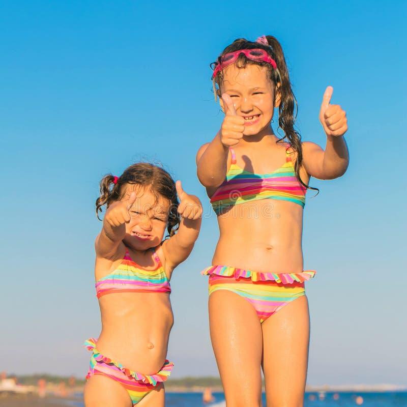 Pulgares de la demostración de los niños para arriba en la playa foto de archivo