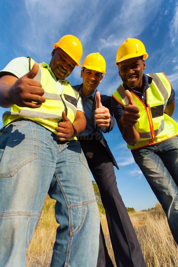 Pulgares de los trabajadores para arriba imagenes de archivo
