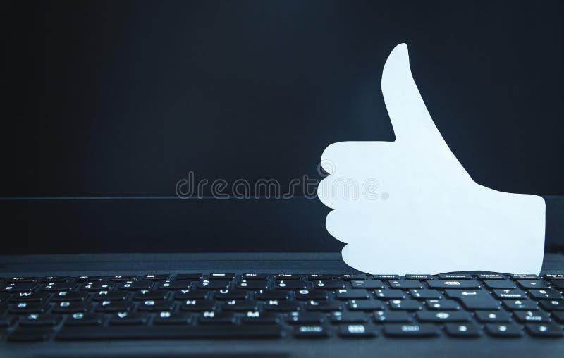 Pulgares de papel encima de la muestra en el teclado del ordenador portátil Concepto social de la red fotografía de archivo