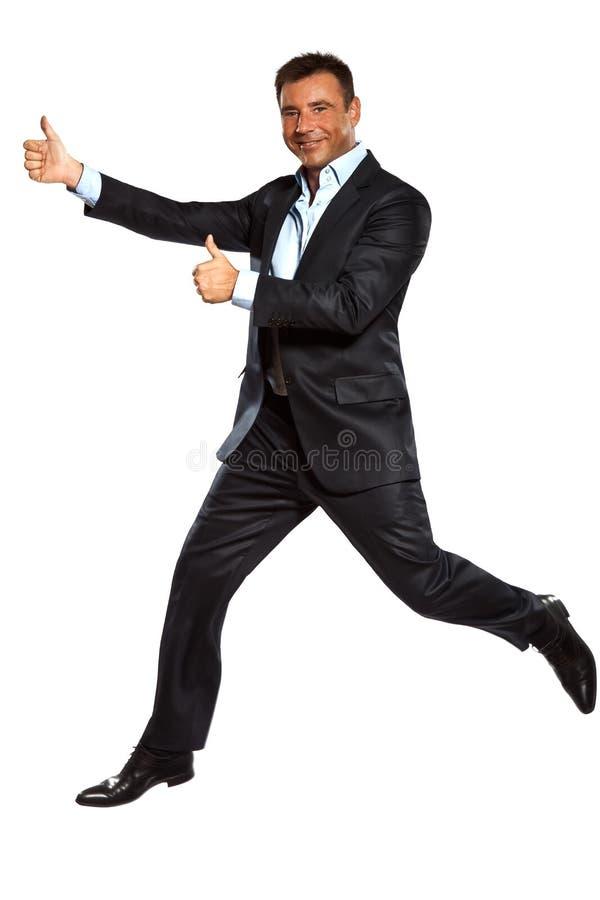 Pulgares dobles de salto que se ejecutan de un hombre de negocios para arriba foto de archivo