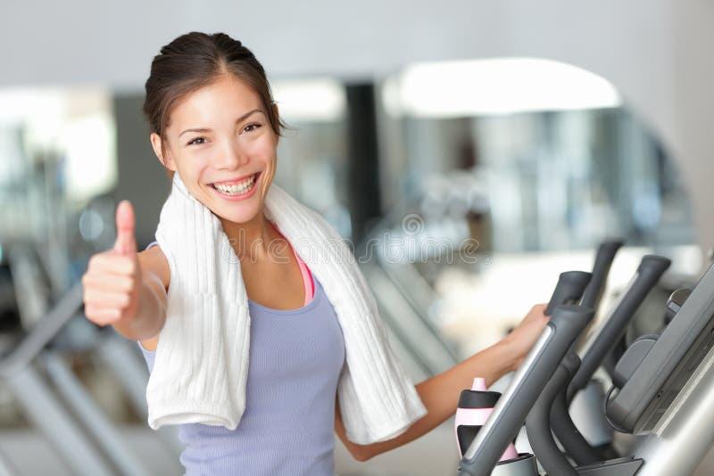 Pulgares felices de la mujer de la aptitud para arriba en gimnasio fotografía de archivo