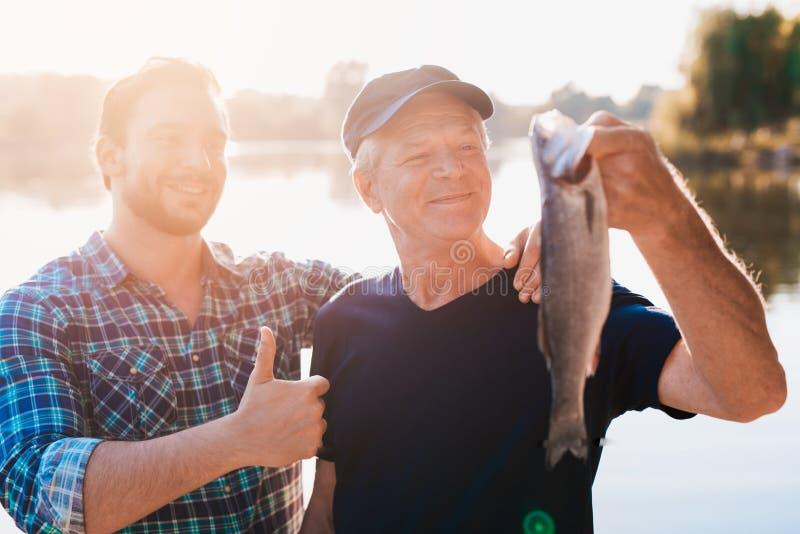 Pulgares para arriba El viejo hombre está sosteniendo un pescado Un hombre se coloca detrás de él con su pulgar para arriba imagen de archivo
