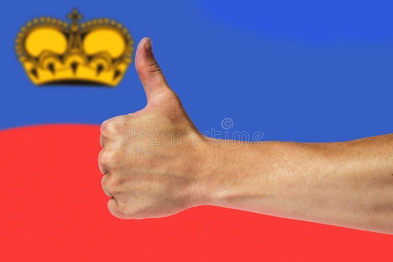 Pulgares para arriba en un fondo de una bandera de Liechtenstein imagenes de archivo