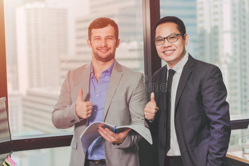 Pulgares permanentes asiáticos y caucásicos del hombre de negocios para arriba y sonrisa feliz foto de archivo libre de regalías